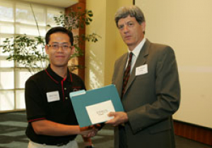 Electrical engineering major Minh Tran receives an award from Stuart Long, interim dean for The Honors College, for his poster presentation at Undergraduate Research Day.