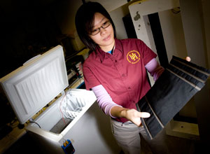 Mechanical engineering graduate student Christiana Chang holds a sheet of carbon nanofiber paper she is embedding in concrete in an effort to create self-heating roads. Photo by Thomas Shea.