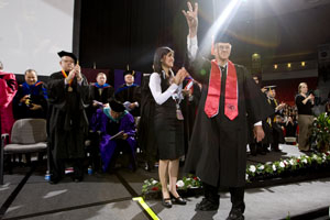 John Rogers stops on stage and flashes a Cougar sign before a packed house at spring commencement Saturday. Photo by Thomas Shea.