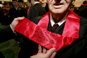 "Toby Hooper, Rogers' grandson, reads the sash presented to his granfather by the Cullen College dean. It reads, ""To John Berry Rogers, Congratulations and Best Wishes, Joe Tedesco, Dean Cullen College of Engineering, May 15, 2010."" Photo by Thomas Shea."