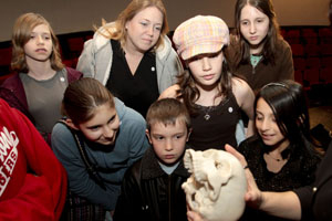 Students with The Friends School get an up close look at the replica skull of Thomas Smith. Photo by Thomas Shea.