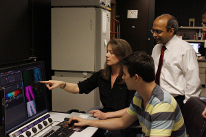 Dr. Badri Roysam and Dr. Leigh Leasure look over brain images with a graduate student researcher.