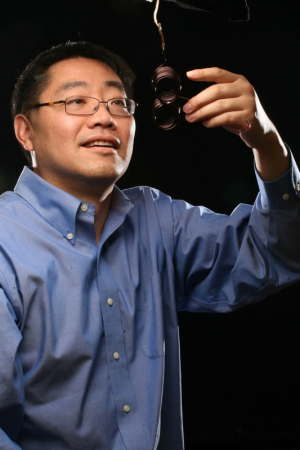 Electrical and Computer Engineering Professor Ji Chen with an electromagnetic coil designed for for brain stimulation.
