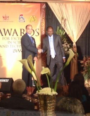 Biomedical Engineering Associate Professor Ravi Birla (left) receives an award for his bioartificial heart research from his home country of Trinidad and Tobago.