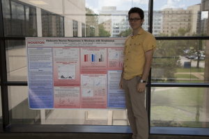 Agaoglu with his award-winning poster from the ARVO conference.