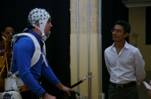 Jose Luis Contreras-Vidal (right) demonstrates his non-invasive brain-machine interface exoskeleton in 2013.