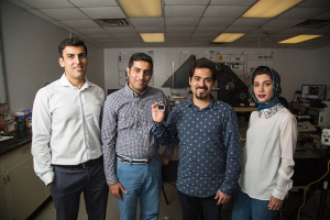 Iceman: Assistant Professor Hadi Ghasemi (far left) is joined by students Seyed Mohammad Sajadi, Peyman Irajizad and Nazanin Farokhnia. Irajizad holds the new magnetic slippery surface.