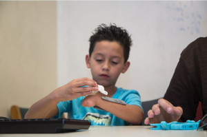 8-year-old Rafael tries on pieces of his gift - a new hand from UH students