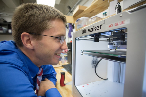 In his lab, Becker watches 3-D printer where many of his robot parts are made