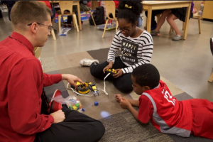 Dr. Becker isn't just playing with robots, he's teaching his students and elementary students