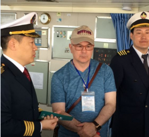 Roberto Ballarini (center) tours the training ship Yukun with a member of the staff and Captain Xinzhuo Liu (far left)