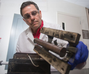 Konstantinos Kostarelos with his prototype that electro-kinetically removes sludge and gunk from crude oil pipes