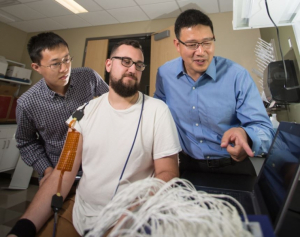 With high-density electrodes placed on the arm of grad student Nick Dias, Yingchun Zhang (far right) monitors muscle contractions to pinpoint the neuromuscular junction. Grad student Chuan Zhang, far left, observes.