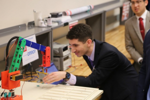 A UH electrical and computer engineering student demos the sorting robot for Omron representatives.