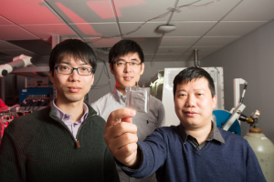 Dr. Yan Yao holds the solid-state battery, with Dr. Yanliang Liang next to him and Dr. Xiaowei Chi behind them at the UH Cullen College of Engineering.