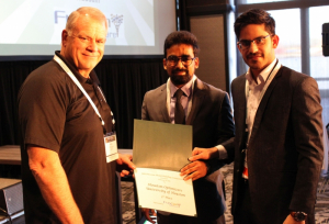 FlexSim CEO Bill Nordgren presents an award to University of Houston graduate students Muhammad Zia-ul-Haq Hussain and Moaz Ahmed for their third place finish at the annual Healthcare Systems Process Improvement Conference.