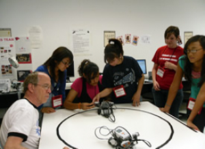 Professor Glover guides campers in building and programming their robot.