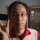Associate Professor Jiming Bao and screen filled with graphene flakes suspended in solvent between two layers of glass. Bao discovered that a magnet rotates and aligns the flakes.