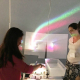 Gwen Musial, (second from right) watches as students use a prism to split white light into a rainbow